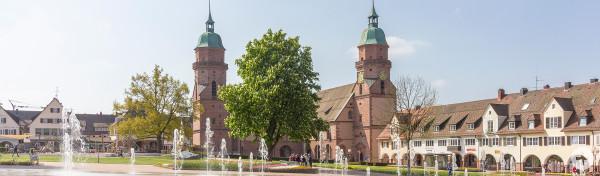 Blick auf die Stadtkirche im Frühling auf dem Marktplatz. Im Vordergrund sprudeln die Fontänen