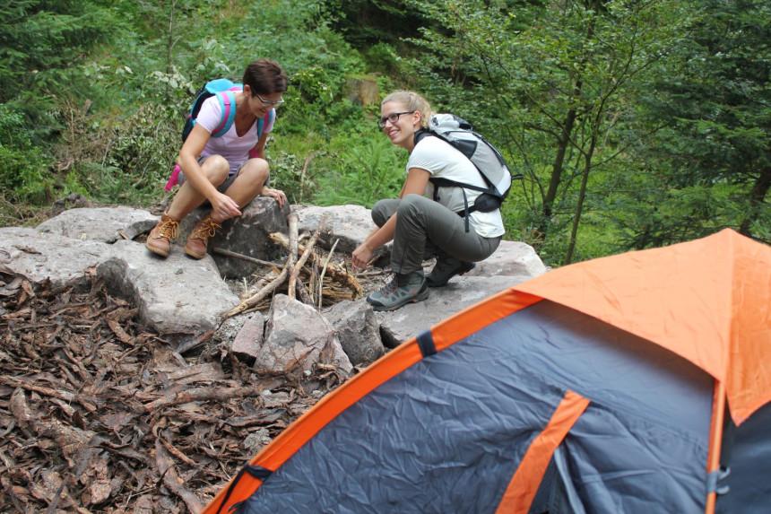 Zwei Frauen machen ein Feuer im Trekkingcamp auf dem Kniebis